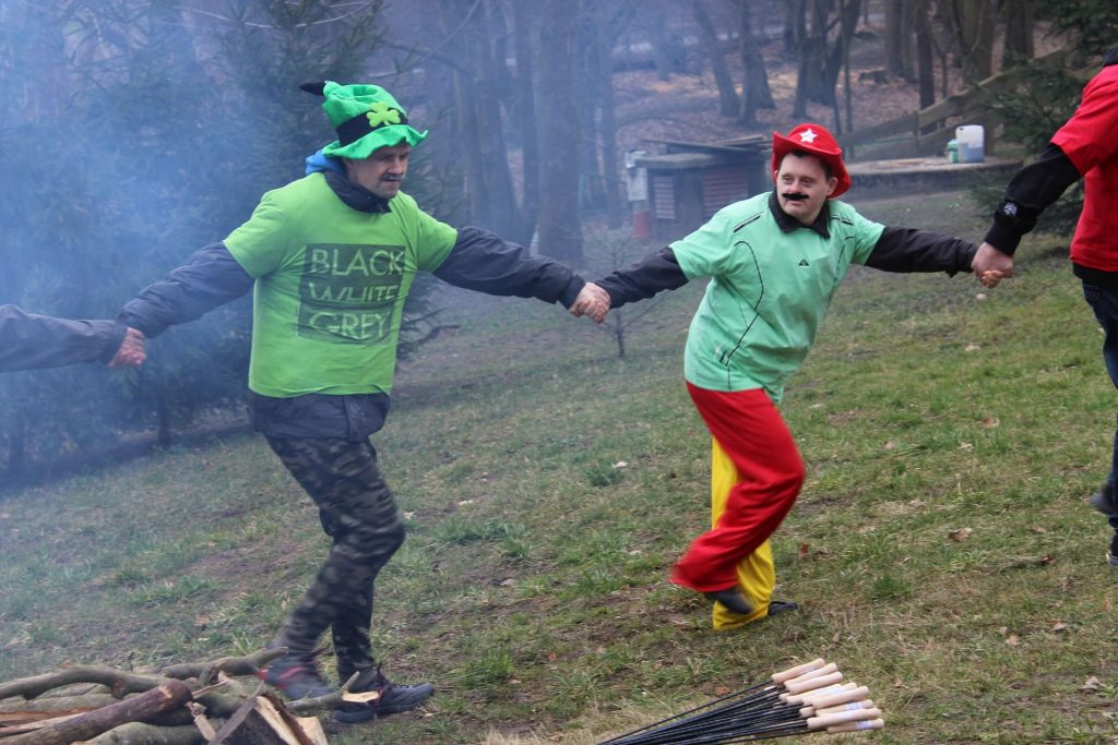Dwóch mężczyzn trzymających się za ręce podczas wspólnego tańca przy ognisku. Podopieczni ubrani w kolorowe stroje witają wiosnę