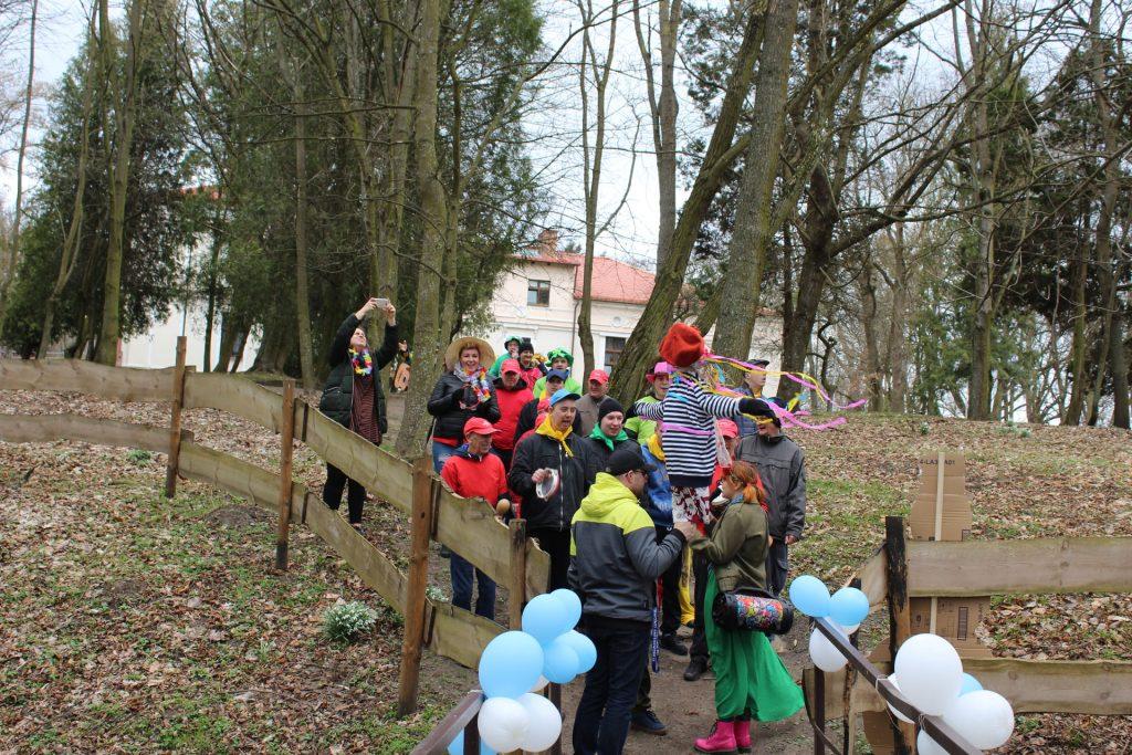 Grupa osób idących przez mały drewniany pomost, na pomoście po obu stronach jasne balony. Przed grupą opiekun z marzanna w rękach