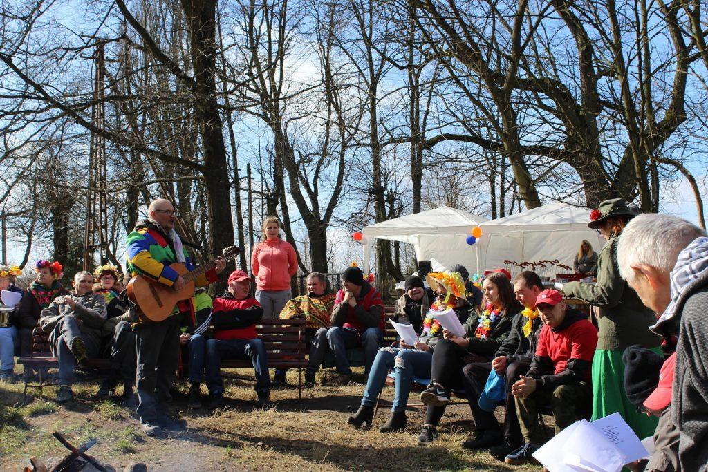 Grupa osób siedzących na ławce, w ręce trzymają śpiewniki. Jedna osoba stoi na środku z gitarą i śpiewa