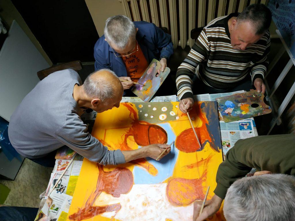 Fotografia przedstawia 4 autorów obrazów, którzy trzymają palety do malowania wraz z pędzlami i malują kolorowy obraz.