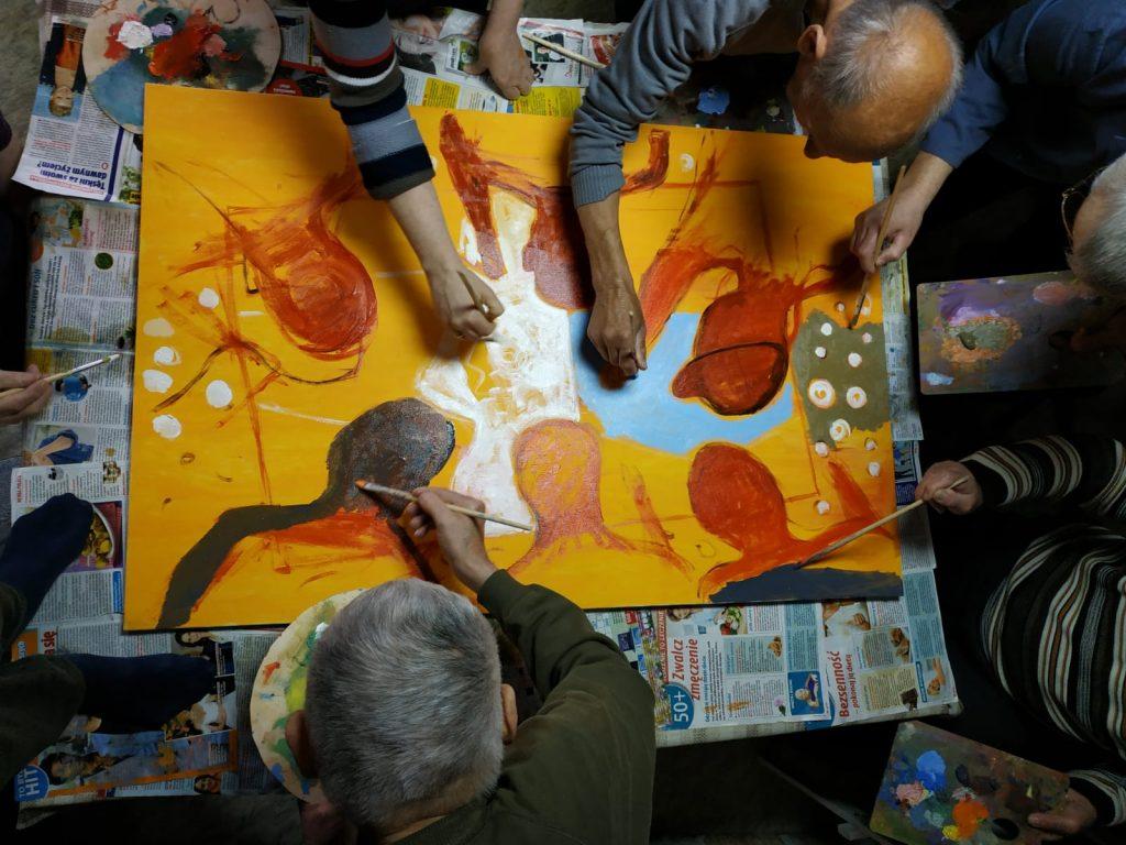 Mieszkańcy podczas malowania obrazów. Zaangażowani malują wspólnie swój obraz robiony z góry