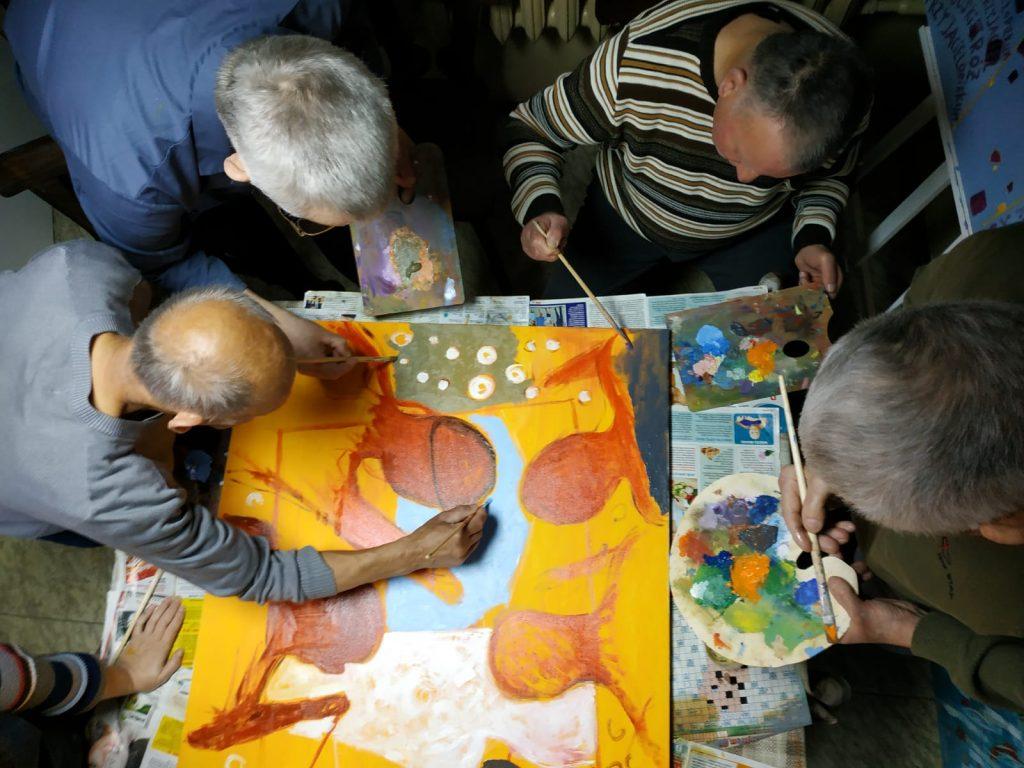 Fotografia przedstawia 4 autorów obrazów, którzy trzymają palety do malowania wraz z pędzlami i malują kolorowy obraz.  Ujęcie przedstawia.