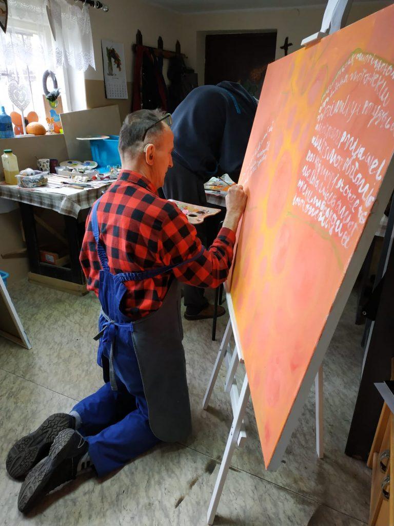 """Ujęcie z tyłu ukazuje jednego z autorów wystawy, który z wielkim zaangażowaniem klęcząc maluje jeden z obrazów na wystawę pt. """"Rokocińska Szkoła Anioła""""."""