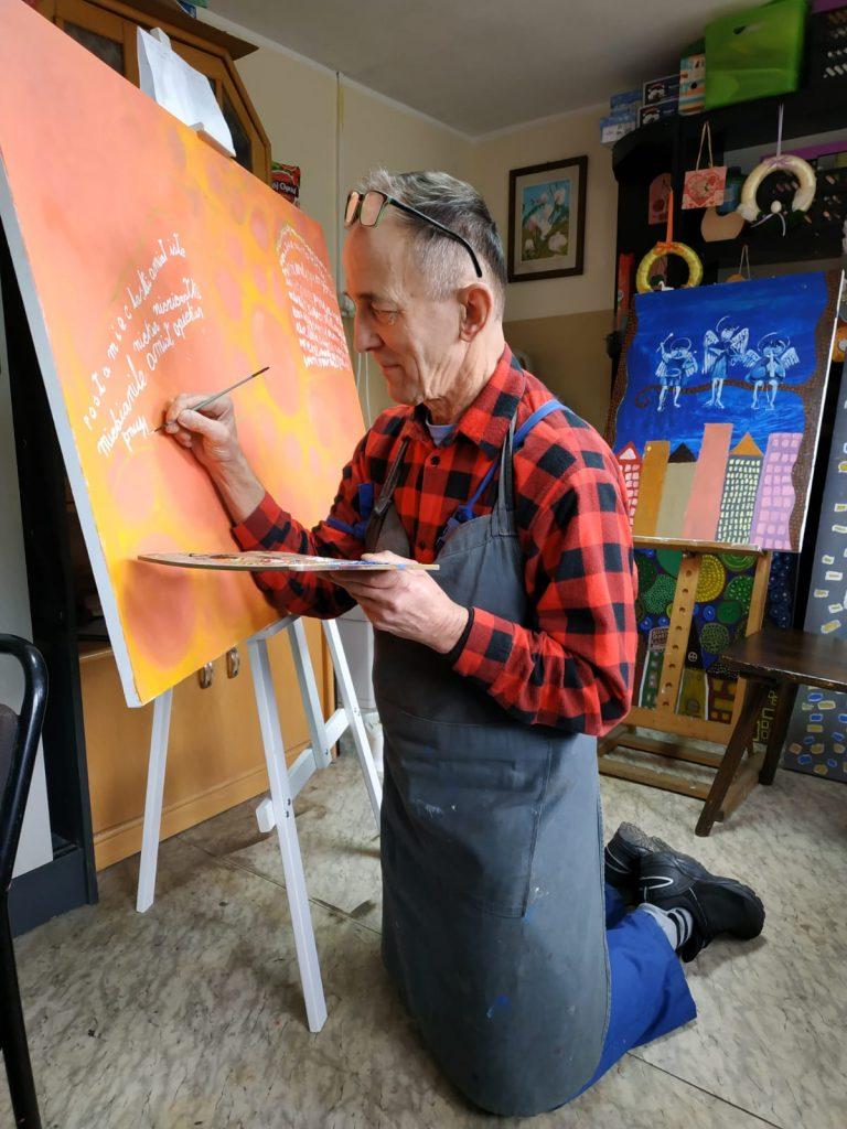 """Jeden z autorów wystawy z wielkim zaangażowaniem klęcząc maluje jeden z obrazów na wystawę pt. """"Rokocińska Szkoła Anioła"""". W tle niewielki obraz ,gdzie nad kolorowymi budynkami trójka aniołów siedzi na gałęzi drzewa."""