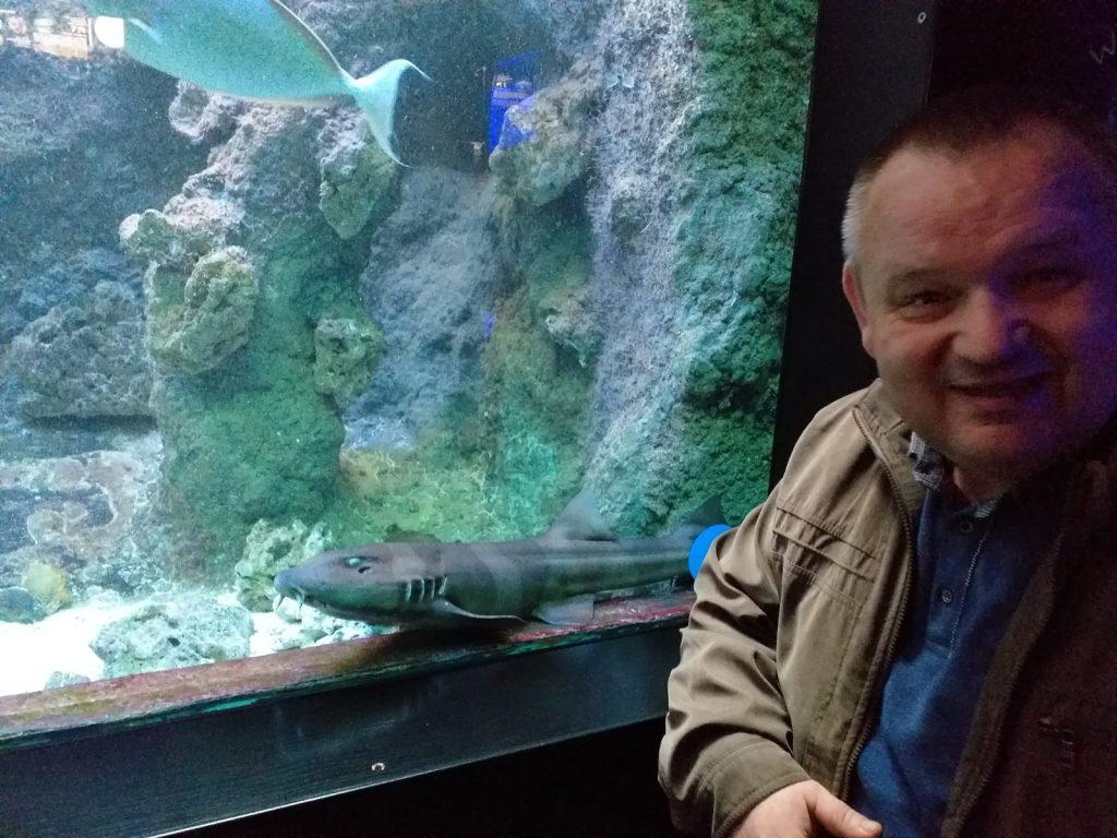 Uśmiechnięty mieszkaniec zwrócony w stronę osoby robiącej zdjęcie. W tle sum w akwarium.