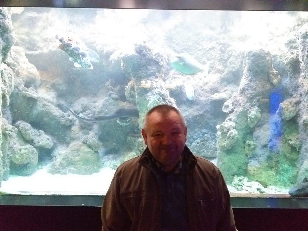 Podopieczny na tle wielkiego akwarium z kolorowymi rybami pozuje do zdjęcia.