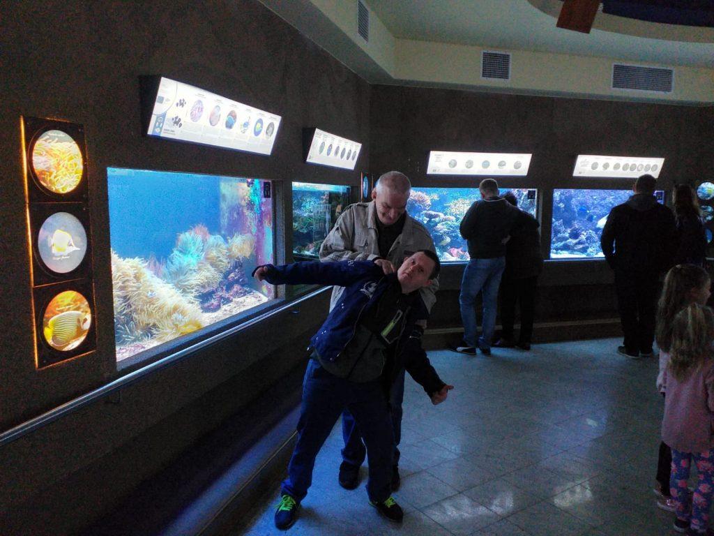 Mieszkaniec trzymający kolegę za ramiona, drugi odchylony lekko do tyłu. Spontaniczna pozycja do zdjęcia na tle czterech akwarium. Nad każdym z akwarium opis ryb oraz żyjątek, które żyją w danym środowisku.