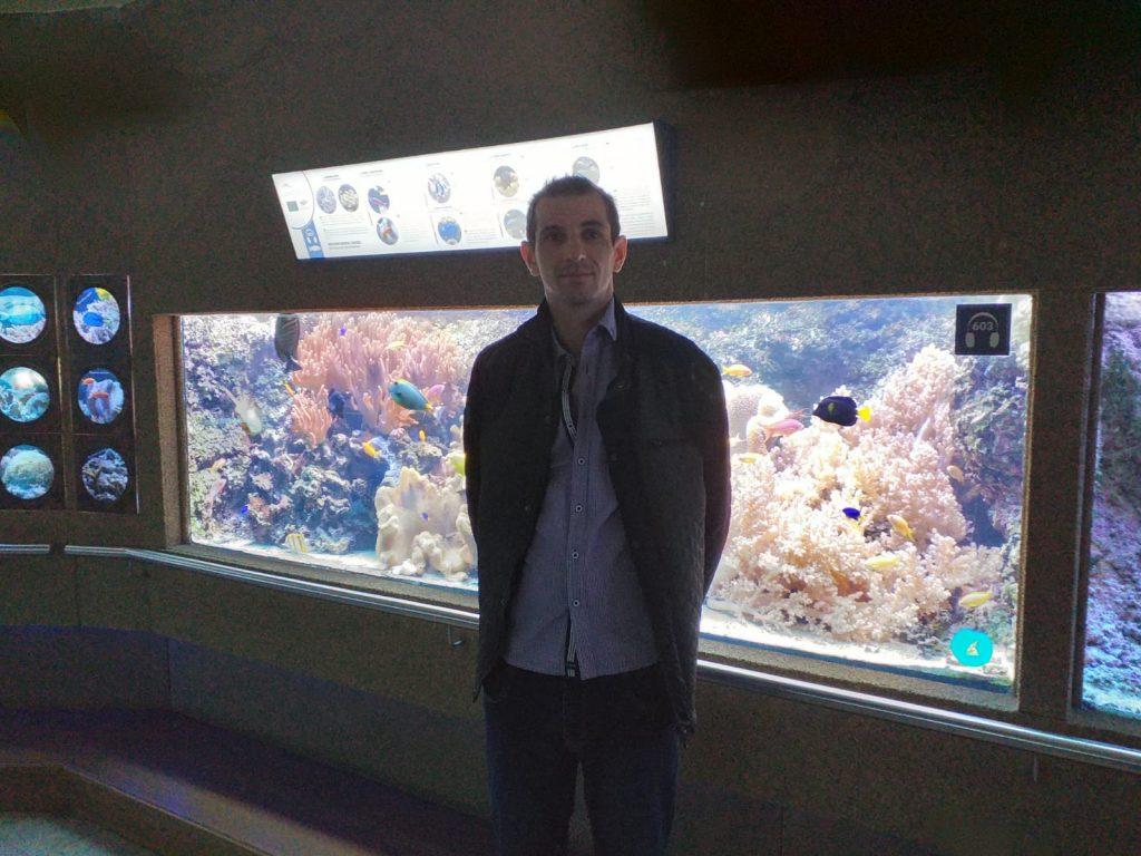 Podopieczny DPS Rokocin stoi na tle wielkiego akwarium pełnego kolorowych ryb.
