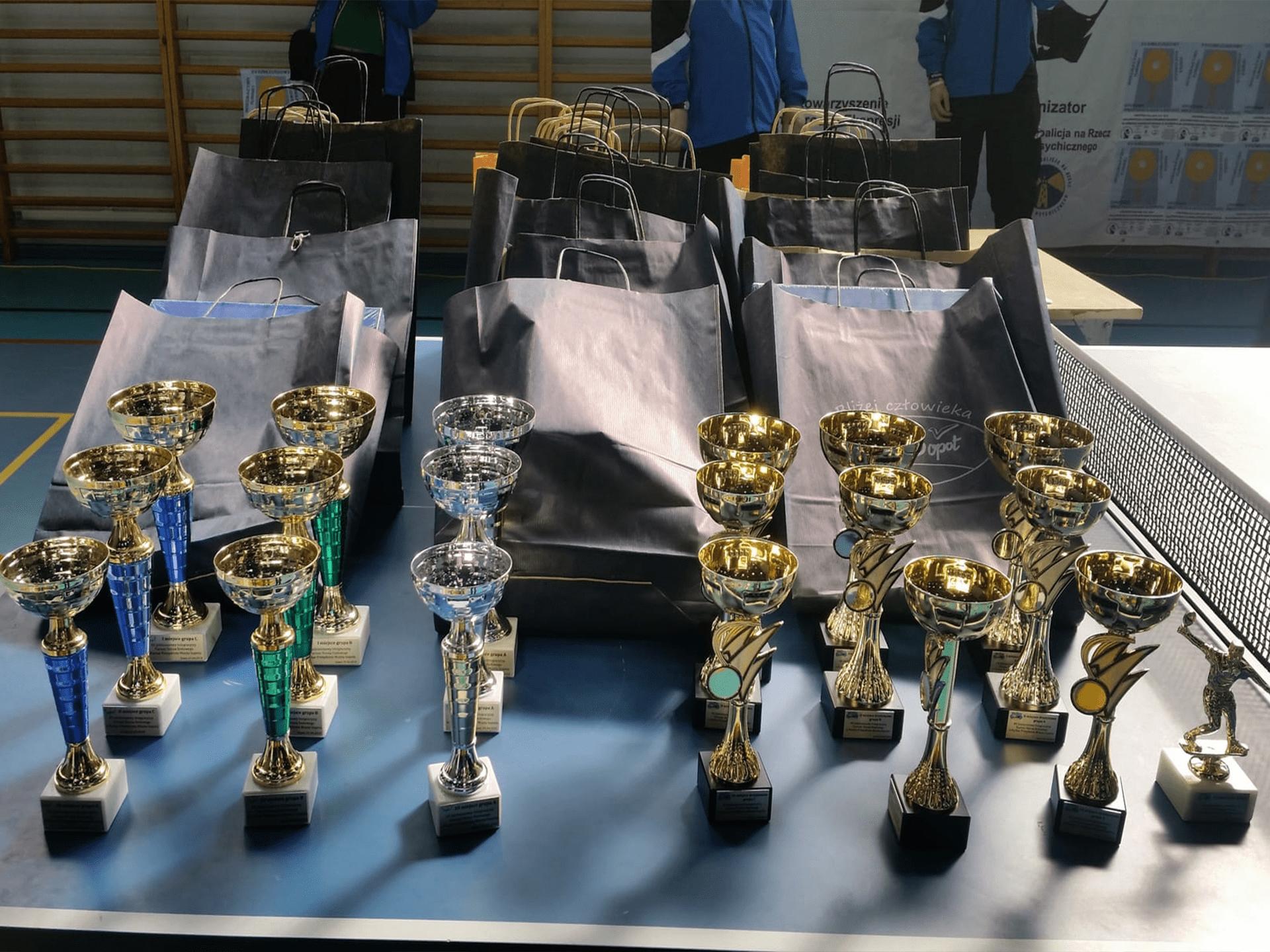 Stos złotych pucharów na inauguracyjnej lidze tenisa stołowego osób niepełnosprawnych.