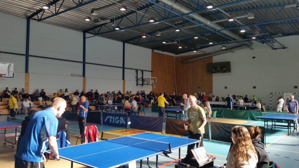Mieszkaniec Małego Domku podczas meczu turniejowego. W tle inni uczestnicy PLTSON rozgrywający spotkania na hali sportowej.