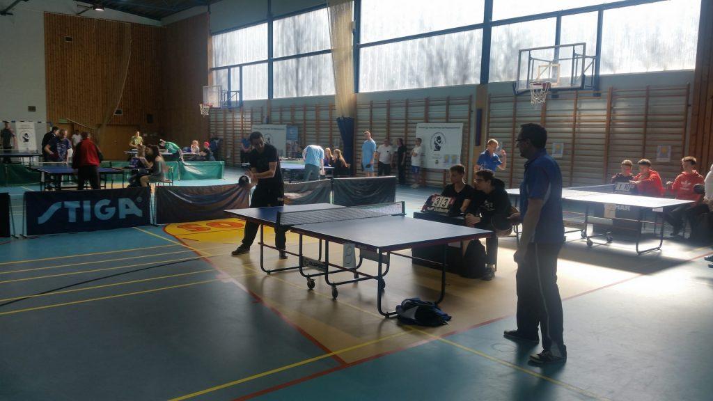 Podopieczny DPS Rokocin w pojedynku z opiekunem drużyny z Rudna. W tle prowadzone są inne pojedynki tenisowe na hali.