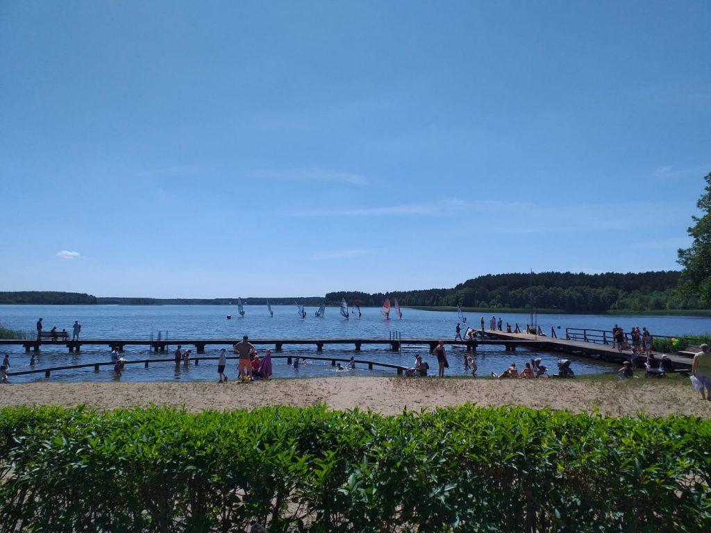Na zdjęciu plaża oraz jezioro w tle lasy oraz bezchmurne niebo.