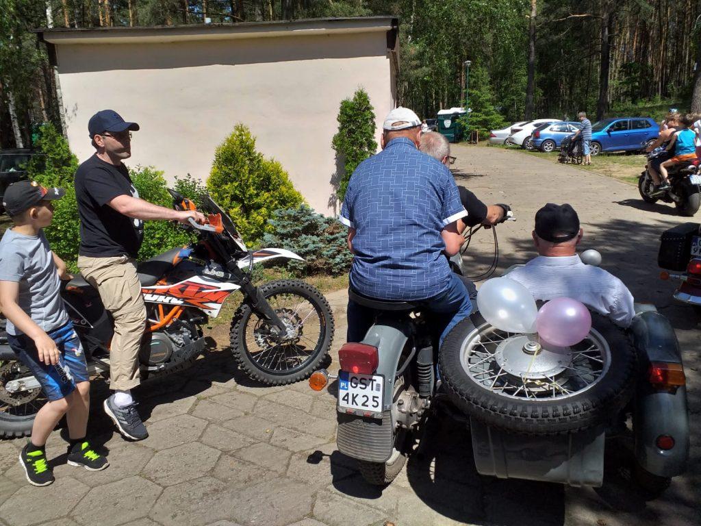 Ujęcie ukazuje 3 motory na jednym z nich mieszkańcy domu siedzą na motorze z dostawką gotowym do jazdy.