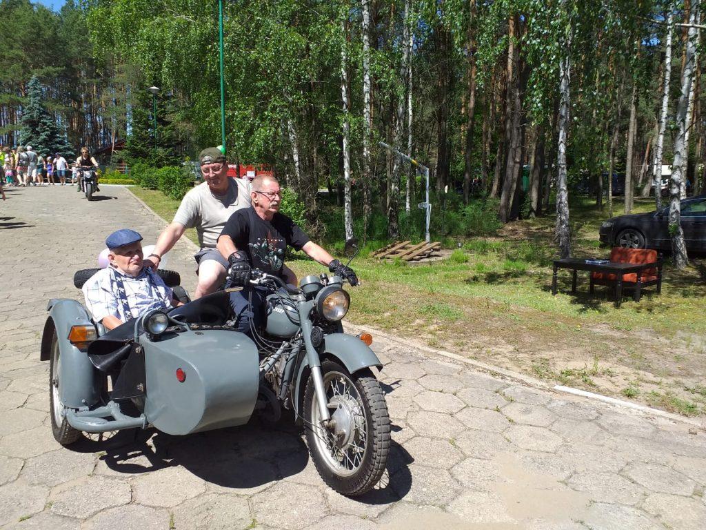 Na motorze z dostawką opiekun wraz z podopiecznym i kierowcą podążają drogą. W tle zielony las.