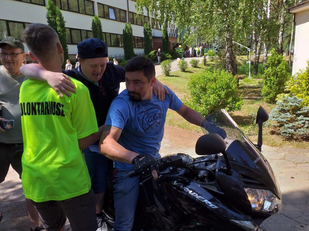 Kierowca oraz wolontariusz pomagają wejść mieszkańcowi za nimi opiekun grupy.
