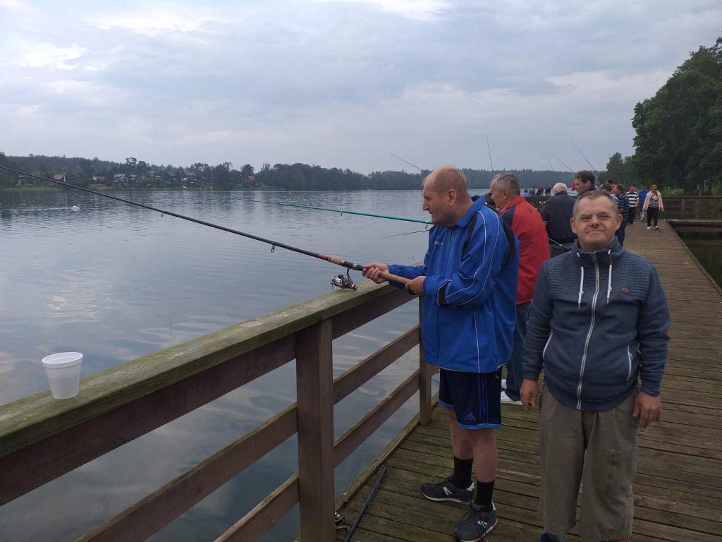 Dwóch mieszkańców stojących na pomoście jeden łowi ryby, a drugi z uśmiechem na twarzy pozuje do zdjęcia