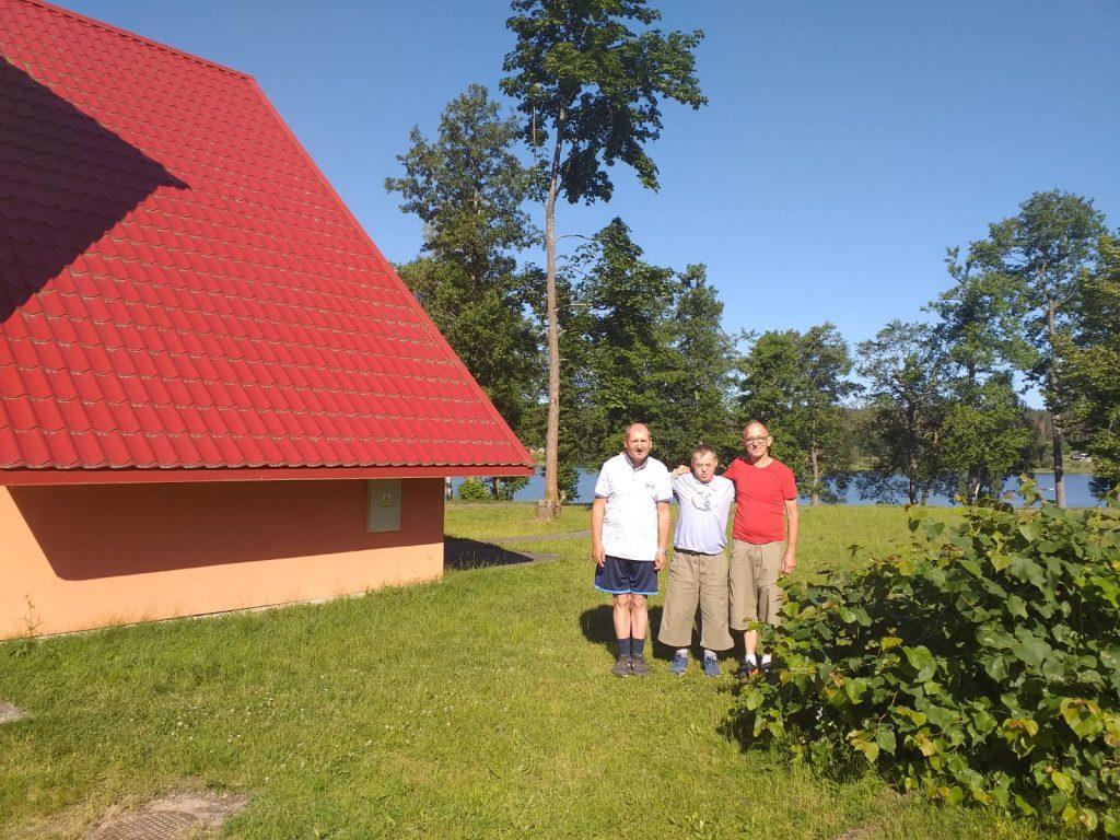 Trójka mieszkańców stojących na zielonej trawie. W tle drzewa i  jezioro.