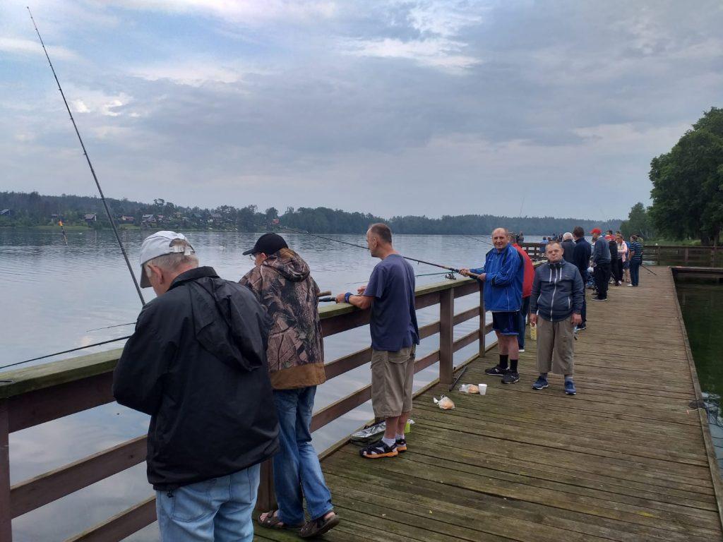 Mieszkańcy stojący na pomoście. Dwóch z nich łowi ryby jeden pozuje
