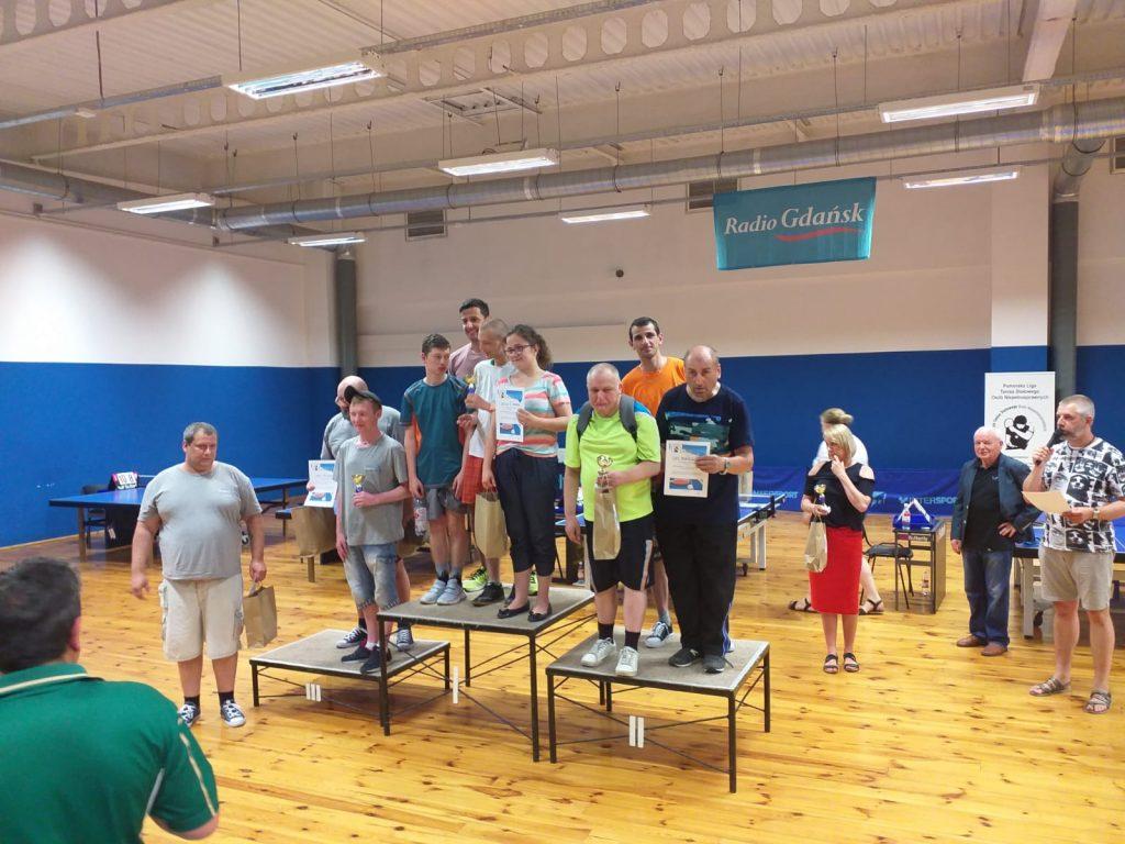 Grupa podopiecznych podczas turnieju tenisa stołowego. Stoją na trzecim miejscu podium. W rękach trzymają nagrody.