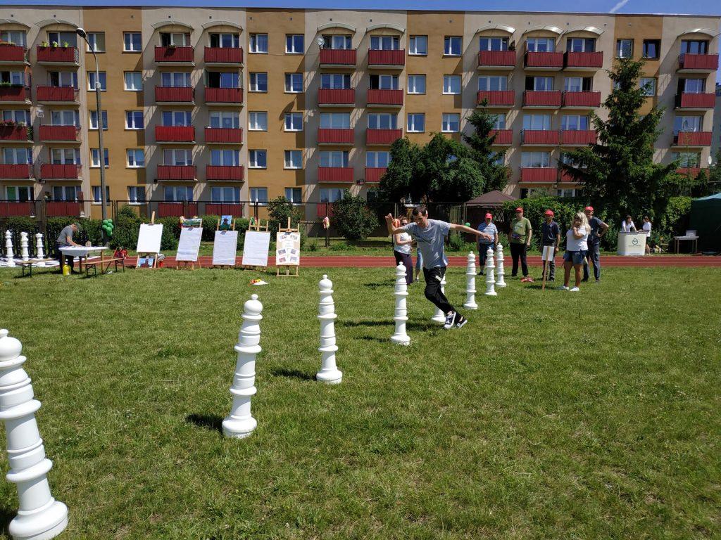 Na zielonej trawie mieszkaniec biegnie slalomem między pachołkami w kształcie pinka do gry w szachy. W tle bloki oraz reszta mieszkańców czekająca na swoją kolej.