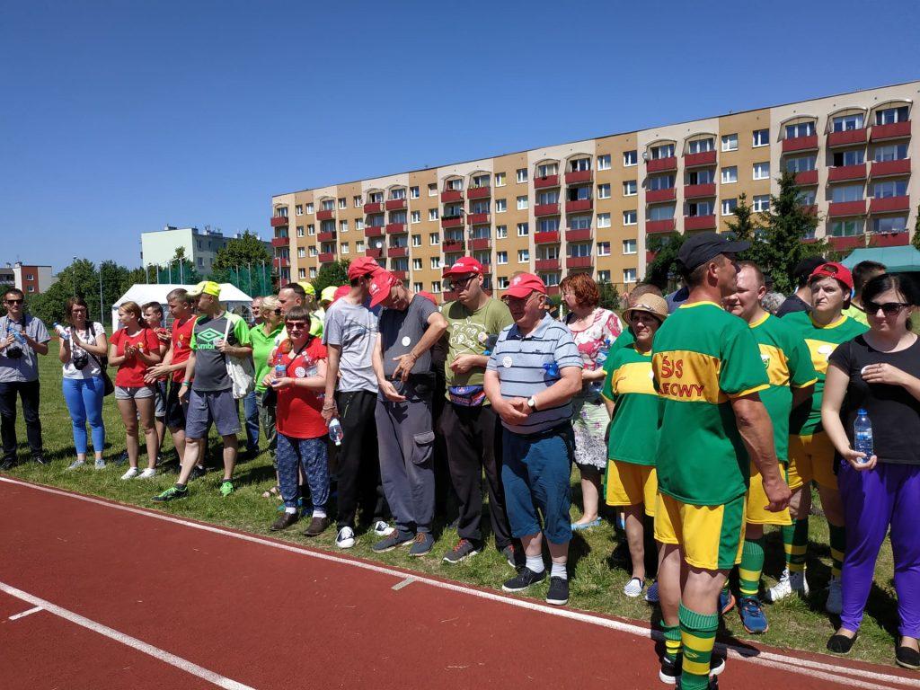 Uczestnicy Turnieju Sportowego stoją w rzędzie i oczekują otwarcia zawodów.