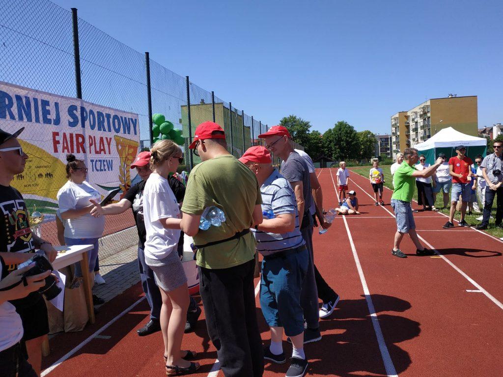 Mieszkańcy odbierają upominki za udział w Turnieju Sportowym.
