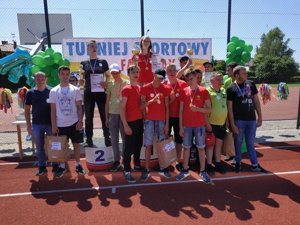 Grupowe zdjęcie uczestników z medalami oraz upominkami.