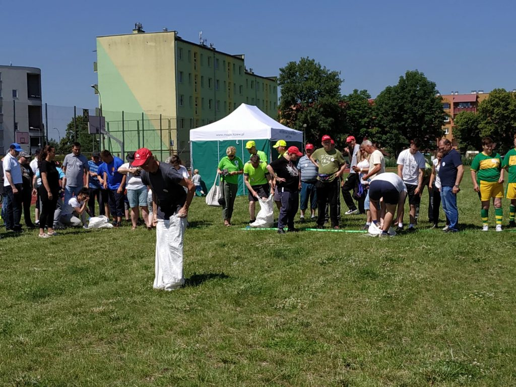 W tle mieszkańcy oraz opiekunowie , dwoje mieszkańców wkłada na nogi worki, a na pierwszym planie mieszkaniec w czerwonej czapce trzyma worek założony na nogi.