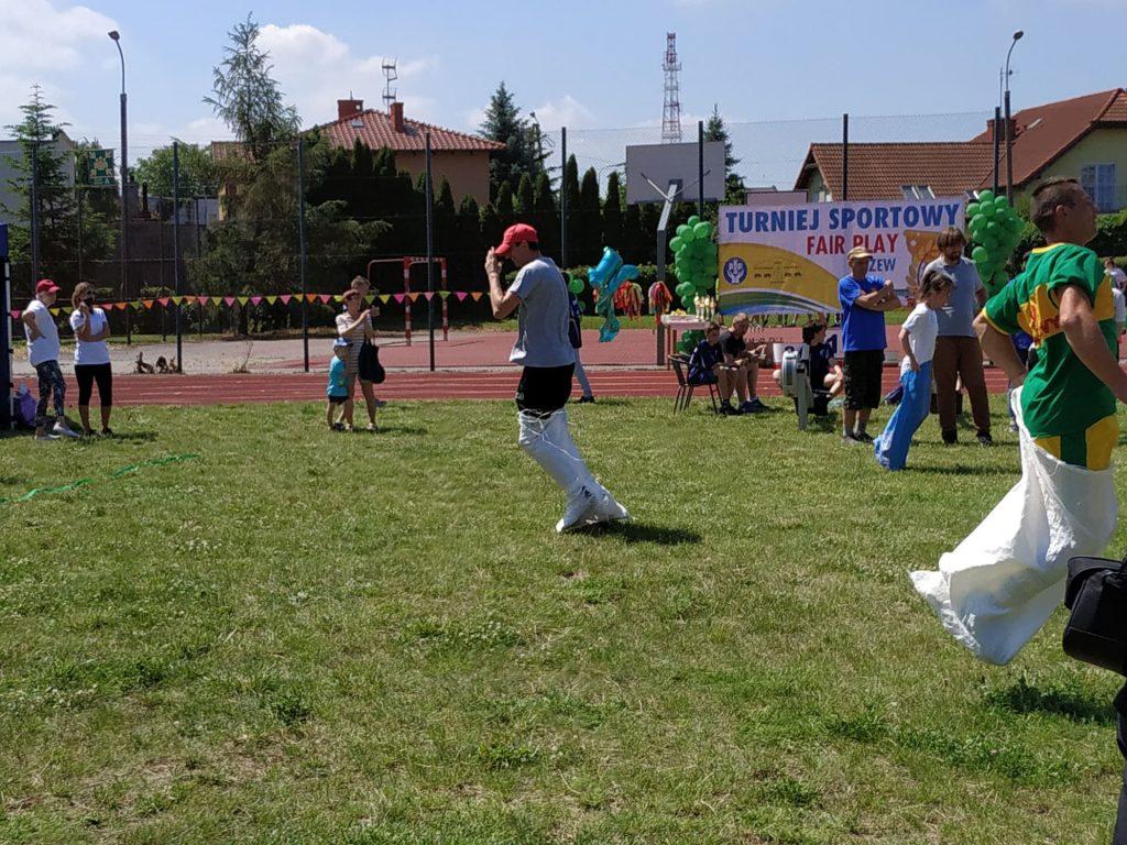 Fotografia przedstawia mieszkańców którzy biorą dział w konkurencji biegu we workach.