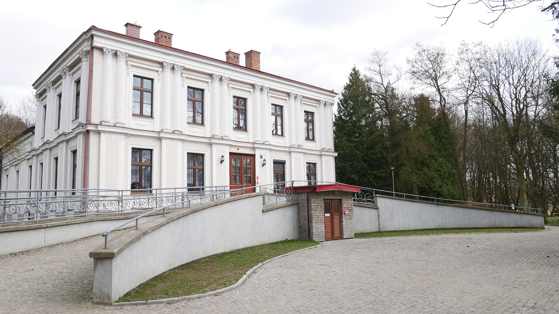 Biały pałac z piętrem, 9 okien z przodu oraz wielkie drzwi. Do drzwi prowadzi podjazd po obu stronach