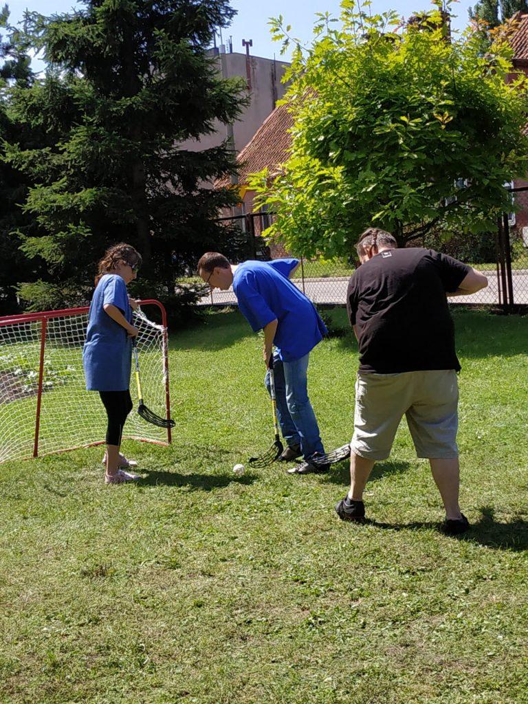Trzy osoby grające na zielonej trawie w unihokeja.
