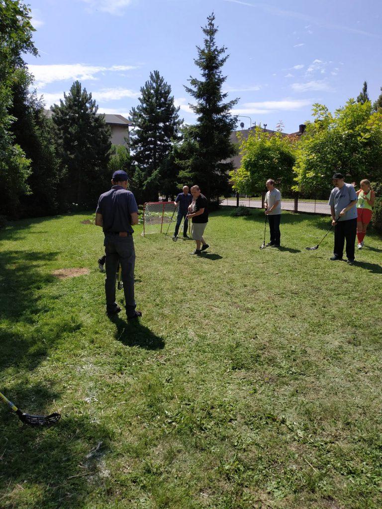 Uczestnicy Turnieju grający w unihokeja na trawie. Słonecznie i zielono wokół.