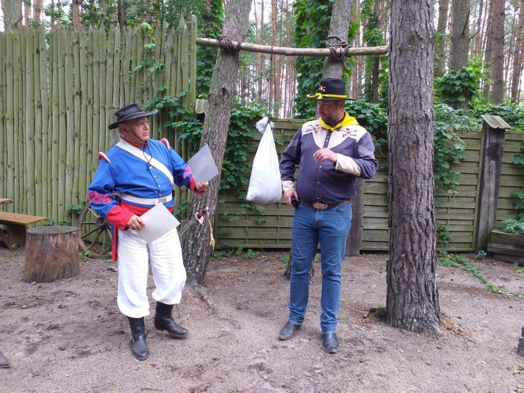 Panowie kowboje przebrani w kolorowe stroje, z butami z ostrogami i kapeluszami na głowach.