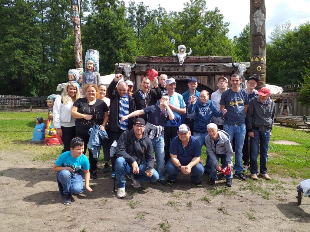 Grupowe zdjęcie przedstawiające wszystkich uczestników wraz z opiekunami stojących nieopodal indiańskiej chaty.