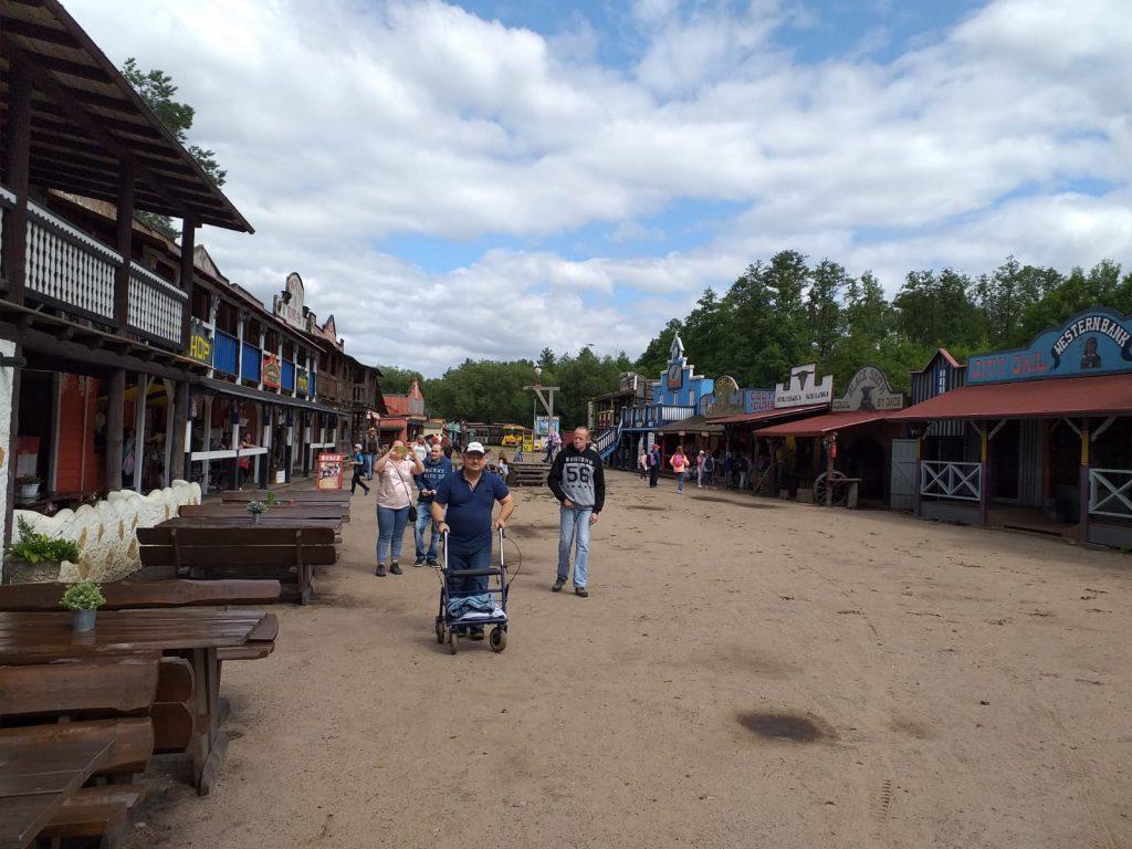 Trójka mieszkańców wraz z opiekunem podczas spaceru w Westernowym miasteczku