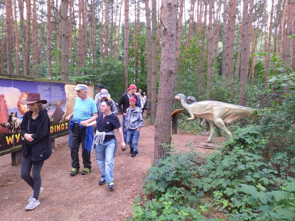 Podopieczni idą wyznaczoną ścieżką i oglądają dinozaury, które stoją między drzewami