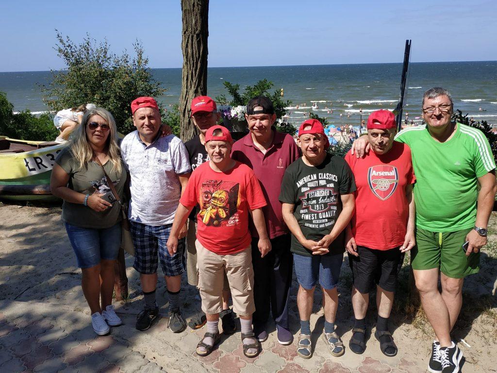 Sześciu mieszkańców wraz z dwoma opiekunami. Wszyscy ubrani w krótkie spodenki i koszulki. Było słonecznie i ciepło w tle  morze.