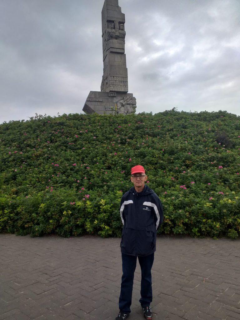 Mieszkaniec ubrany w długie ciemne spodnie i kurtkę, na głowie ma czerwoną czapkę z daszkiem w tle pomnik na Westerplatte