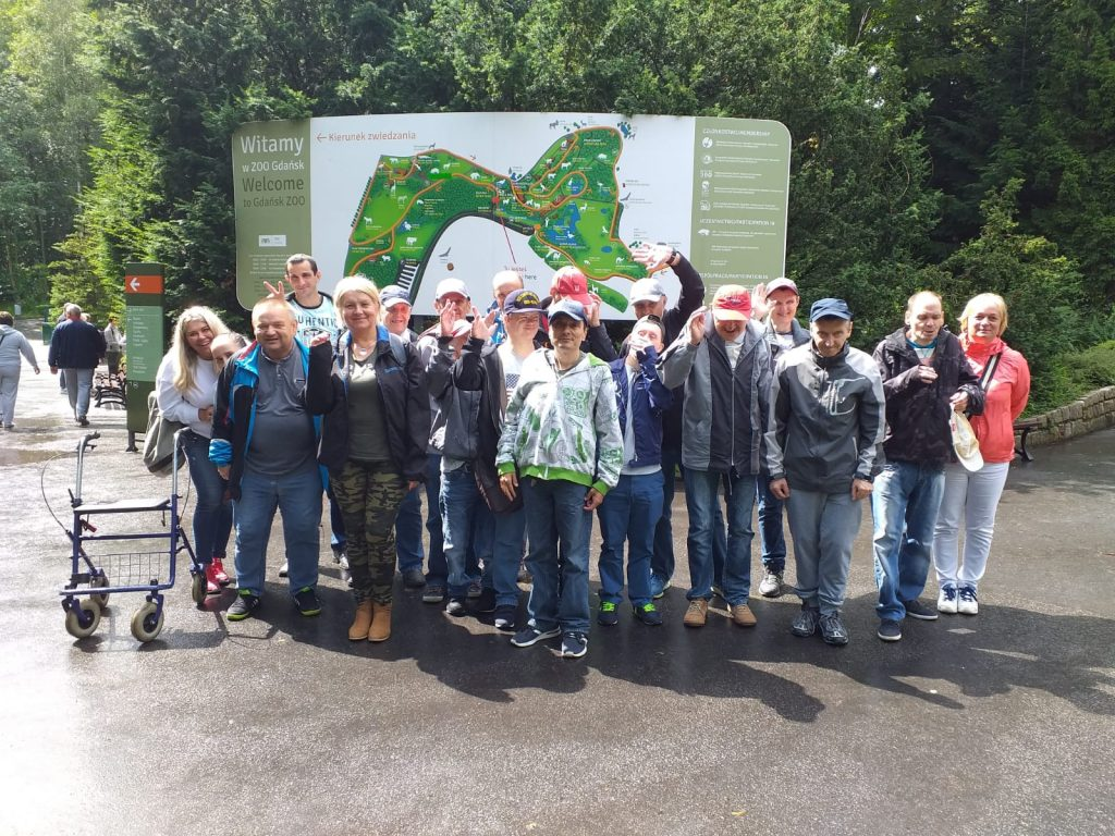 Grupa mieszkańców Domu Pomocy Społecznej stojąca przed mapą ZOO w Gdańsku
