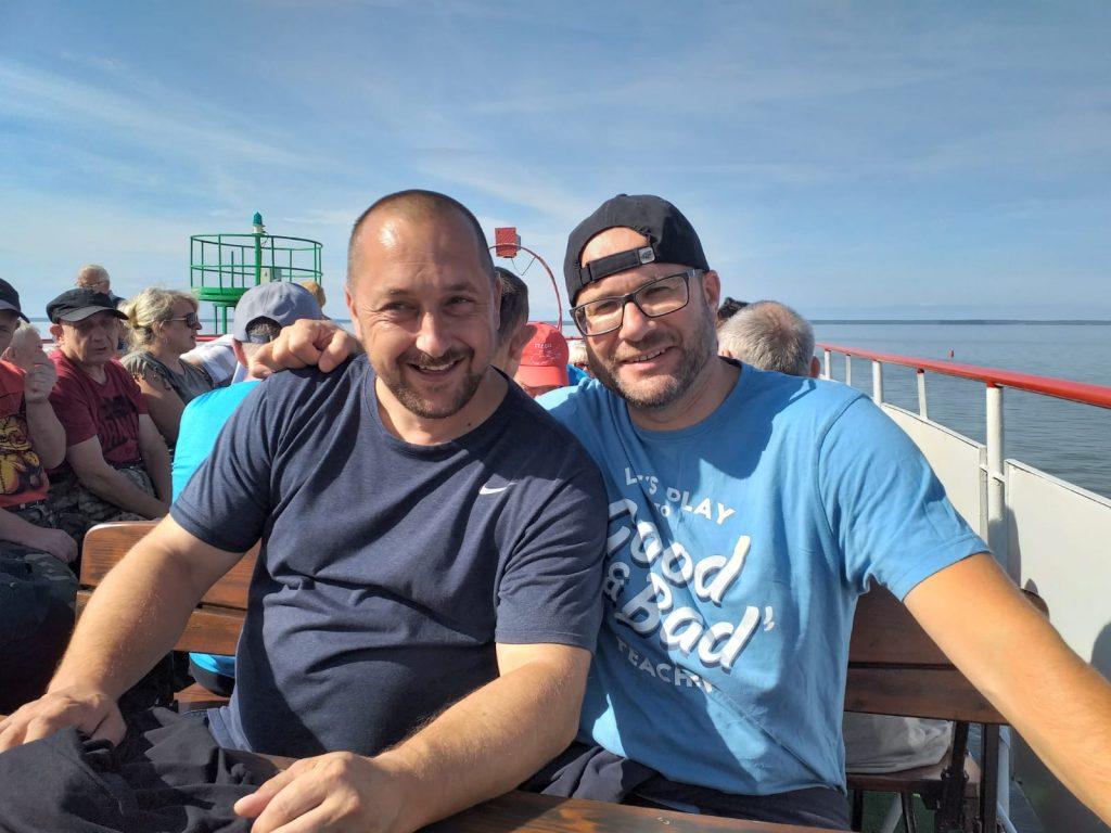 Dwóch uśmiechniętych opiekunów grupy podczas rejsu na statku