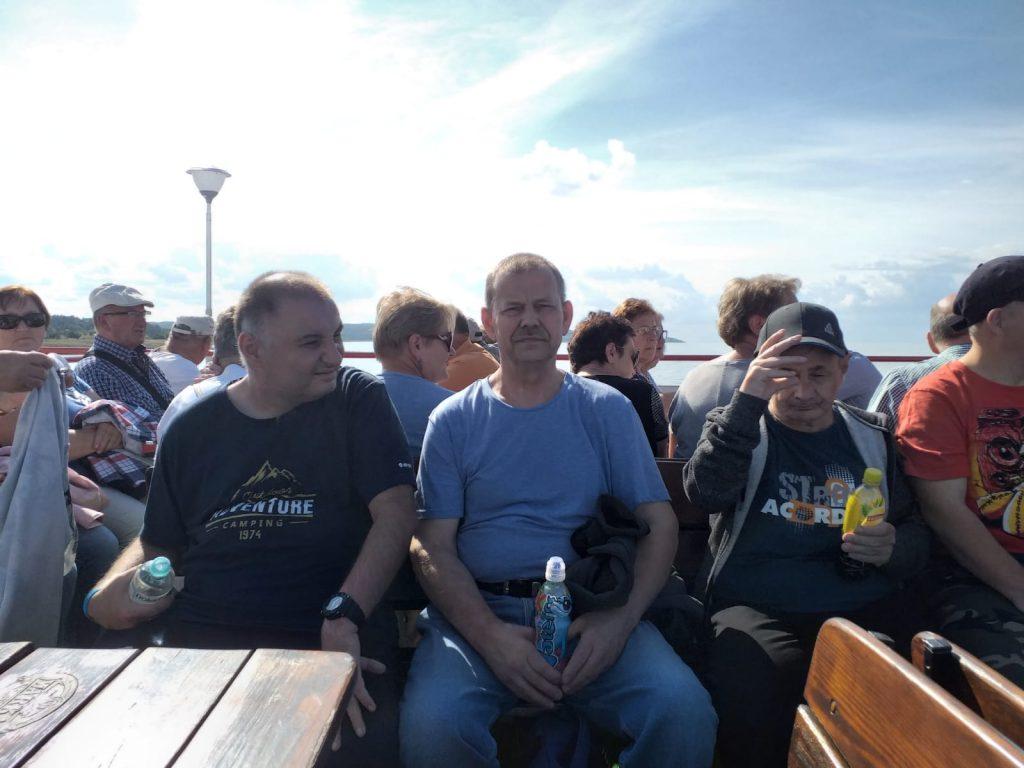 Mieszkańcy podczas rejsu statkiem. Siedzą wspólnie i się rozglądają