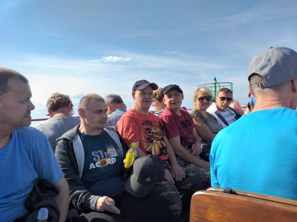 Grupa ludzi oraz paru mieszkańców siedzących wspólnie na statku.