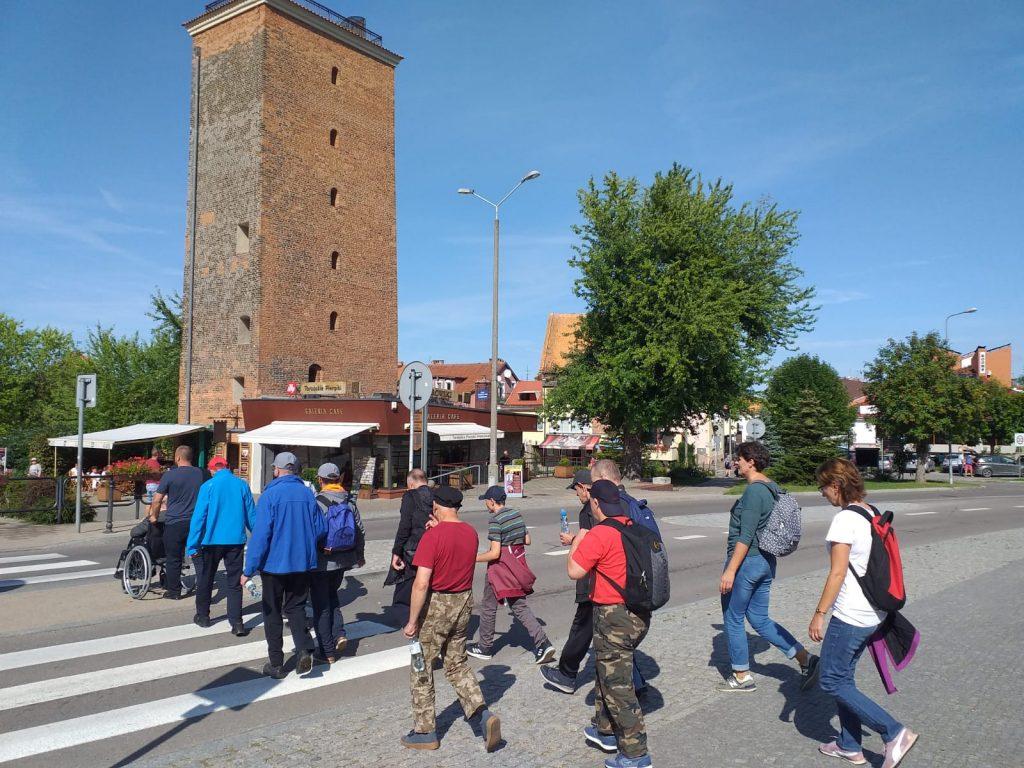 Grupa mieszkańców przechodząca przez pasy w tle wysoka czerwona wieża z wieloma oknami