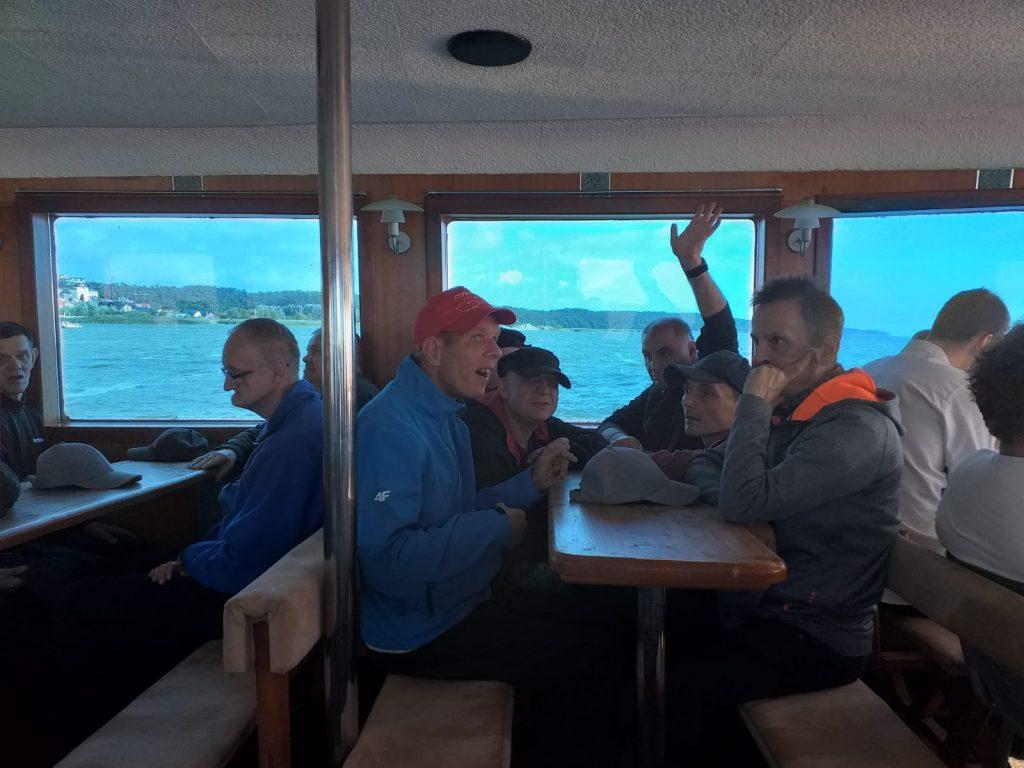 Grupa mieszkańców na statku siedząca pod pokładem