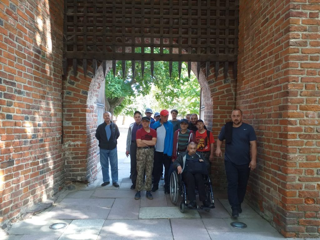 Uczestnicy wycieczki stoją w bramie starego zamku nad nimi krata z ostrymi kolcami.