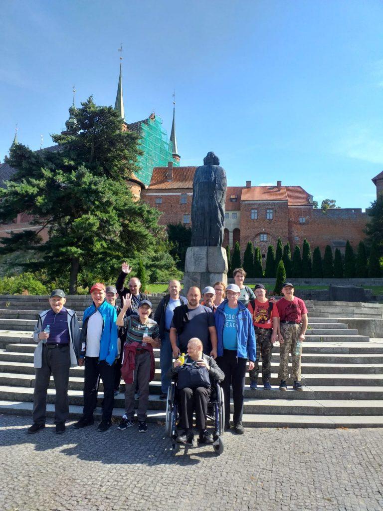 Uczestnicy wycieczki stojący na schodach przy pomniku Kopernika nieopodal Domu Kopernika.