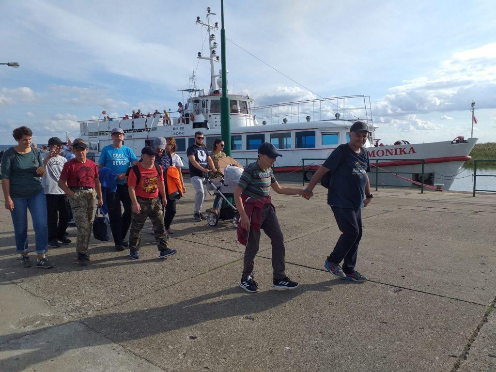 Mieszkańcy idący przystanią w tle statek o nazwie Monika