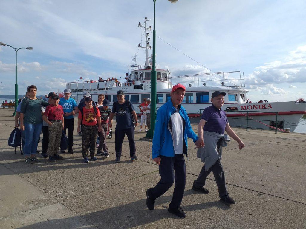 Grupa mieszkańców idących wspólnie w tle statek Monika