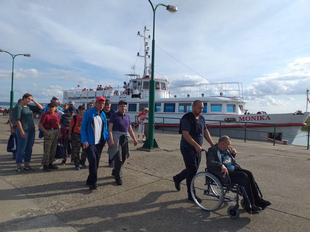 Grupa mieszkańców DPS Rokocin z przodu grupę prowadzi opiekun pchający mieszkańca na wózku