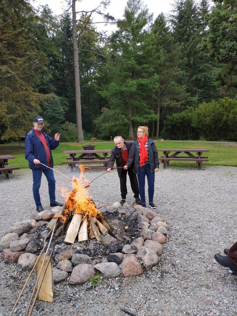 Trzy osoby stojące przy ognisku, smażą kiełbaskę.